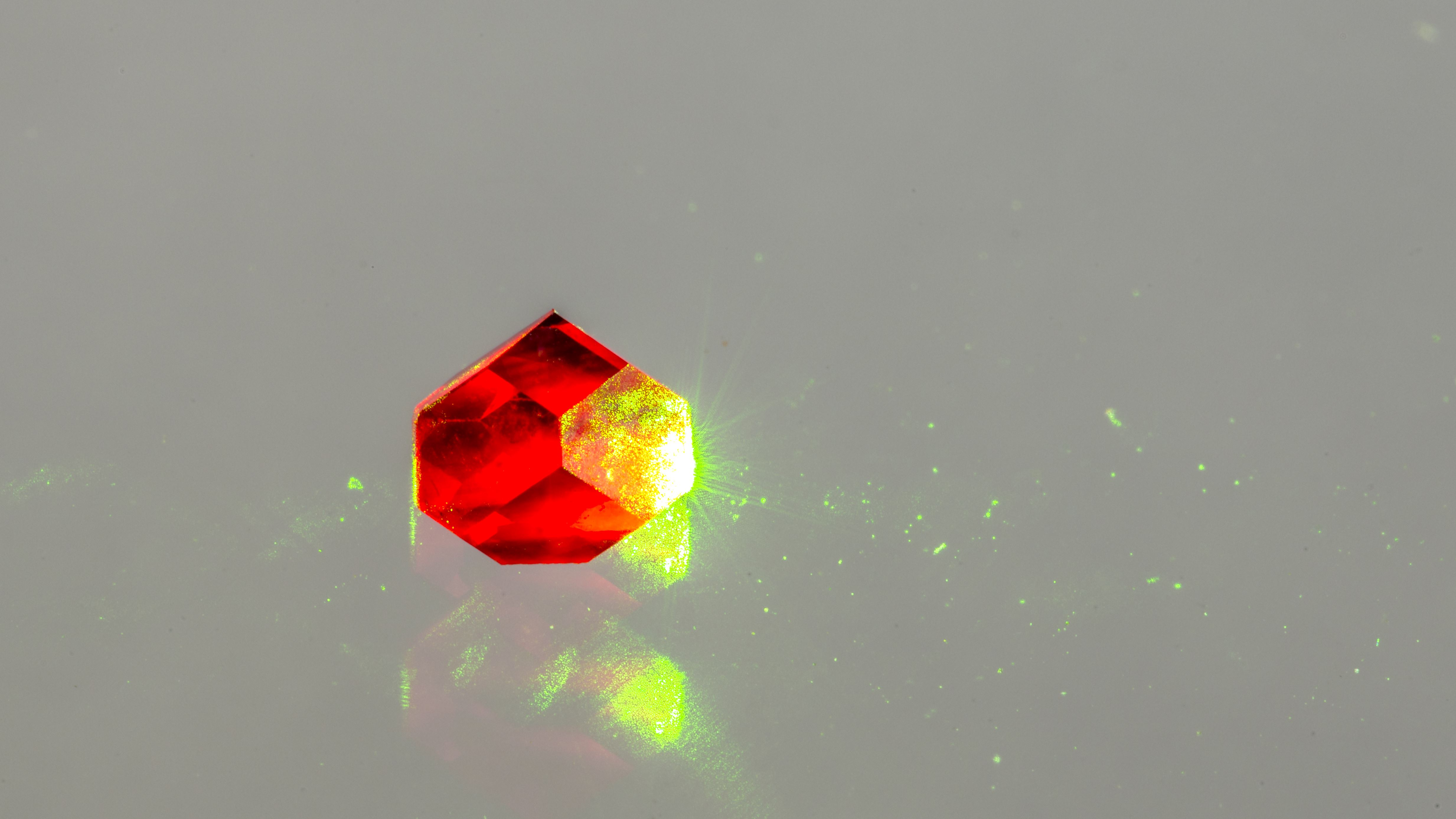 Photograph of diamond containing nitrogen vacancies fluorescing due to illumination with green light. Credit: Jon Newland