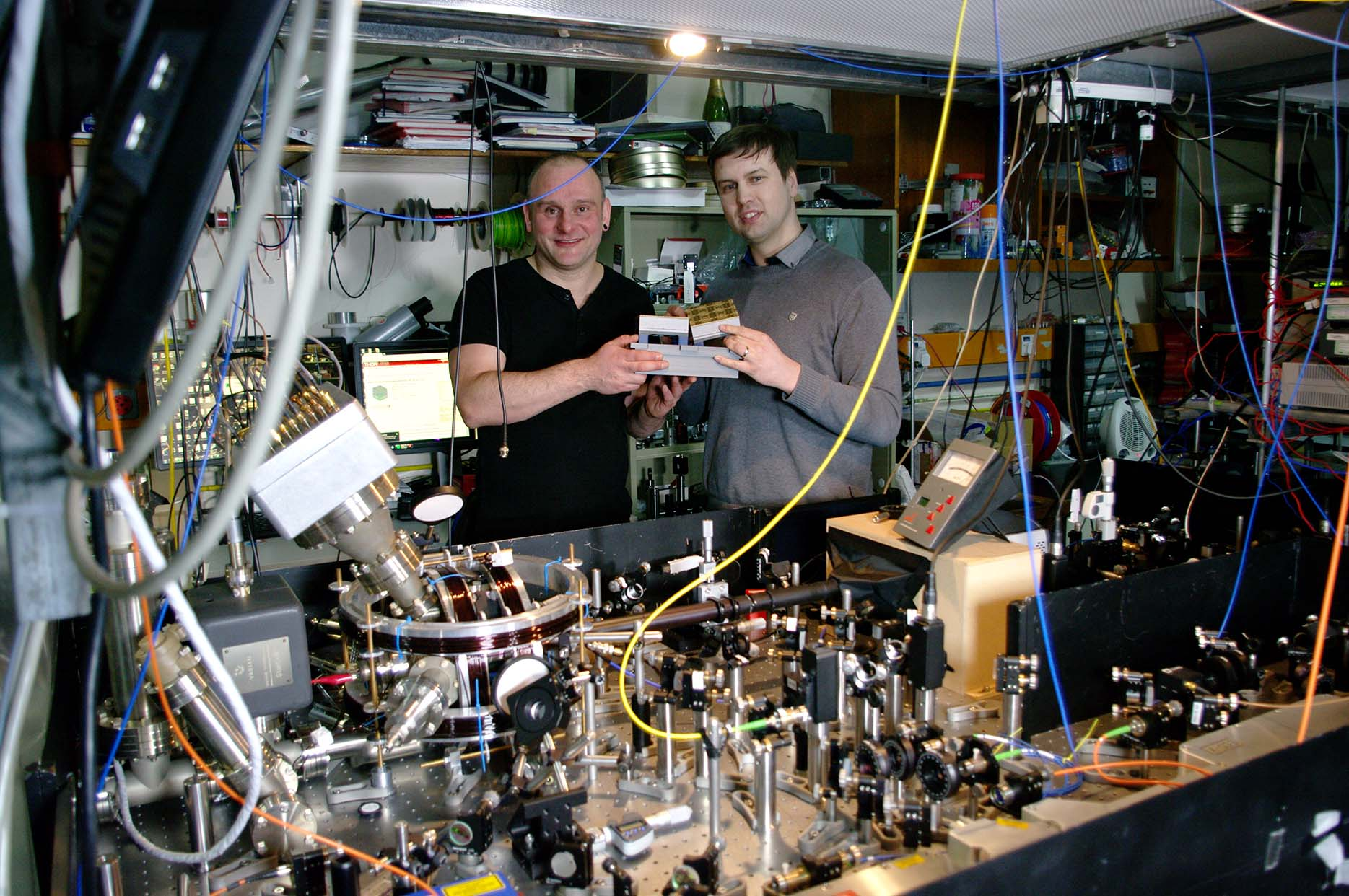 Prof. Hensinger (left) and Dr Lekitsch (right) with a quantum computer blueprint model behind a quantum computer prototype at the University of Sussex.