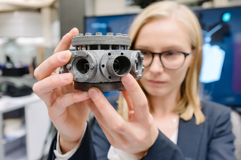 Amy Hughes holding a model of an ion trap vacuum system